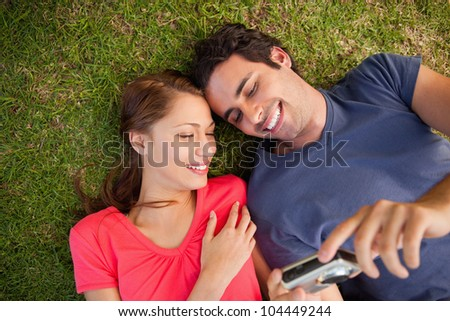 Two friends smiling while looking at photos on a camera as they lie side by side on the grass