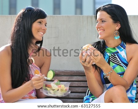 Two friends - smiling young women eating together outdoors on sunny day