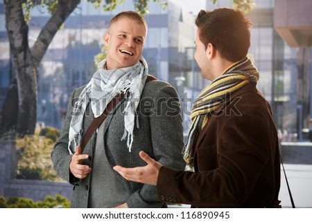 Two friends standing outside of building, chatting, laughing.