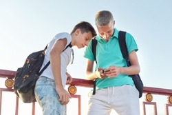 Two friends teenage boys using smartphone, talking and smiling, outdoor summer day, sunset on the bridge