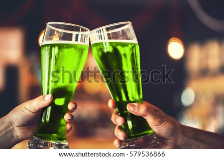 Two friends toasting with glasses of green beer at the pub with free space for your text. Beautiful background of the Oktoberfest and St. Patrick's day. fine grain. Soft focus. Shallow DOF