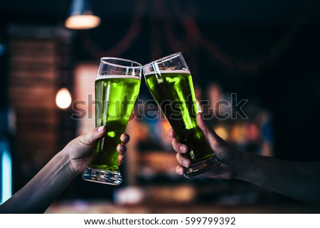 Two friends toasting with glasses of green beer at the pub with free space for your text. Beautiful background of the Oktoberfest and St. Patrick's day. fine grain. Soft focus. Shallow DOF.