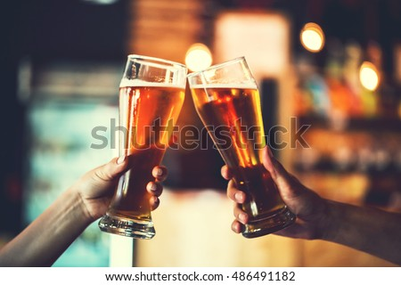 Two friends toasting with glasses of light beer at the pub. Beautiful background of the Oktoberfest. fine grain. Soft focus. Shallow DOF #486491182