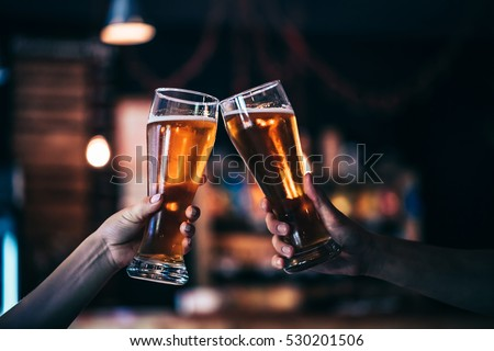 Two friends toasting with glasses of light beer at the pub. Beautiful background of the Oktoberfest. fine grain. Soft focus. Shallow DOF.