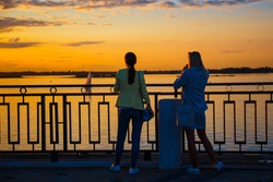 Two friends tourists on the waterfront enjoy a beautiful sunset. Travel, vacation.