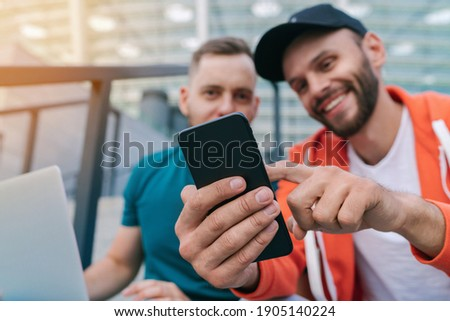 Two friends using mobile phone and laptop for betting during soccer play ready to celebrate victory of favourite team. Men using gambling application while sitting on stadium steps. Focus is on hand. Сток-фото ©