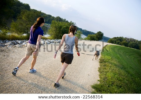 two friends walking a dog