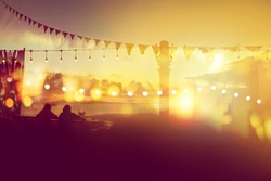 two friends watching sunset at restaurant on the beach, blurred bokeh light on sunset with yellow string lights decor in beach restaurant