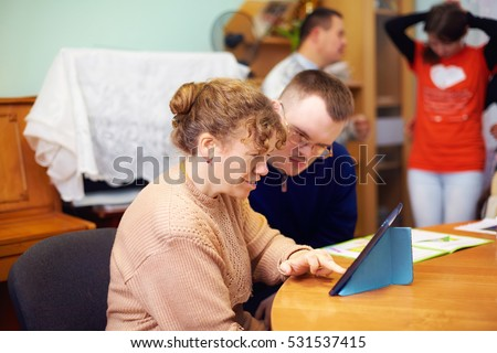 two friends with disability in rehabilitation center, watching digital tablet