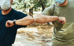 Two friends with facial mask greet each other with the elbow before starting a country walk. New safe greeting rules.