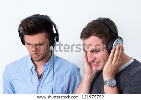 Two friends with headphone listening to music in front of a white background