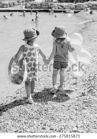 two friends with rings walking hand in hand on the summer beach ( black and white )