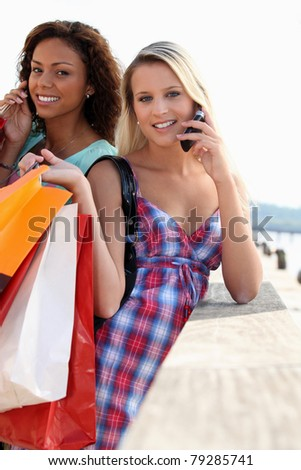 Two friends with shopping bags holding mobile phones