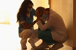 Two frustrated doctors in medical protective masks sit in corridor of hospital. Irregular working hours for healthcare workers in coronavirus pandemic concept