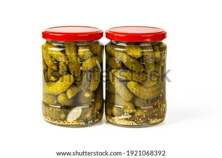 Two full glass jars of pickled gherkins isolated on a white background. Whole green cornichons marinated with dill, garlic and mustard seeds. Crunchy baby pickles. Tasty canned vegetables. Front view. Photo stock ©
