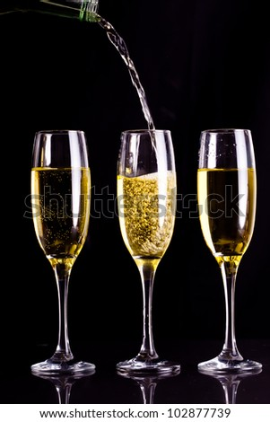 Two full glasses of champagne and one being filled against black background - stock photo
