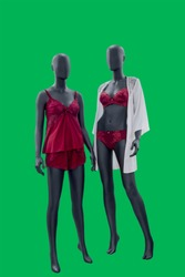 Two full-length female mannequins wearing fashionable nightwear, isolated on green background. No brand names or copyright objects.