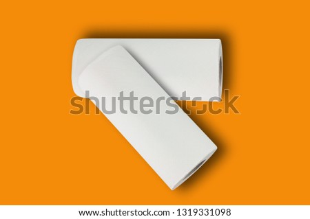 Two full rolls of white soft paper towels or paper for toilet in center on orange table. Top view