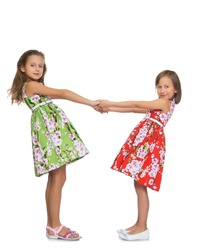Two fun girls to hold hands - Isolated on white background