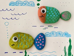 two funny fish are drawn on sea pebbles, against the background of the animated sea