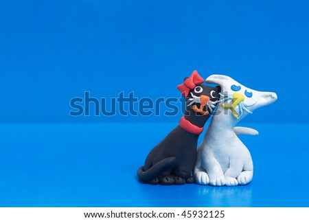 Two funny friendly plasticine black and white cats. Blue copyspace for greeting text