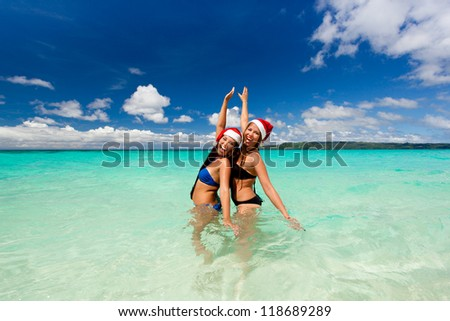 Two funny girls in santa hat on beach, celebrating Christmas