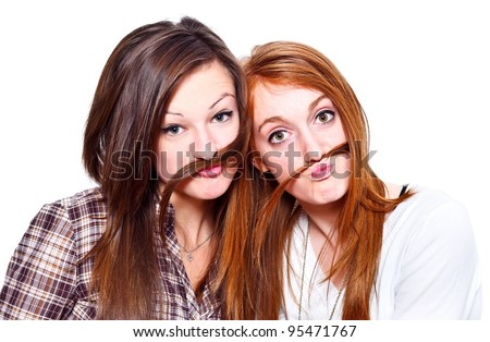 Two funny girls making mustache of their hair