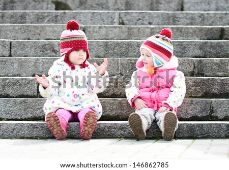 two funny girls sitting on the stairs