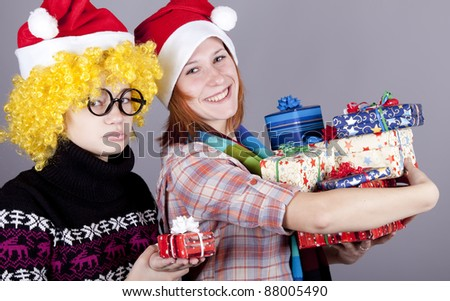 Two funny girls with christmas gifts. Studio shot.