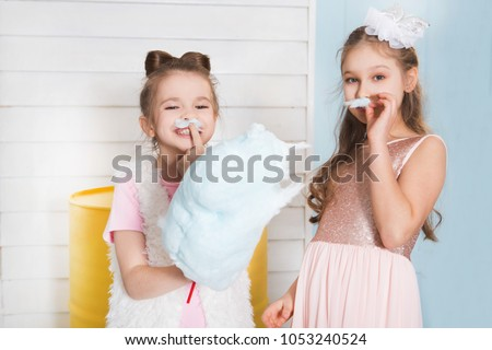Two funny girls with cotton candy posing on a children's holiday #1053240524