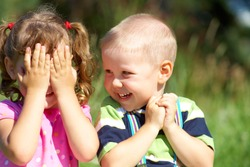 Two funny kids are playing, covering his face with his hands