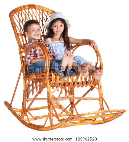 Two funny kids sitting in the rocking chair together, isolated on white
