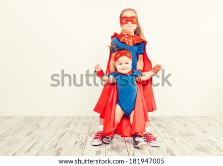 Two funny little power super hero kids in a blue raincoat. Superhero concept