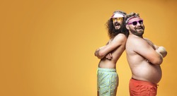 Two funny men wearing swimming shorts, vacation concept