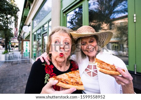 Two funny senior women eating street food pizza
