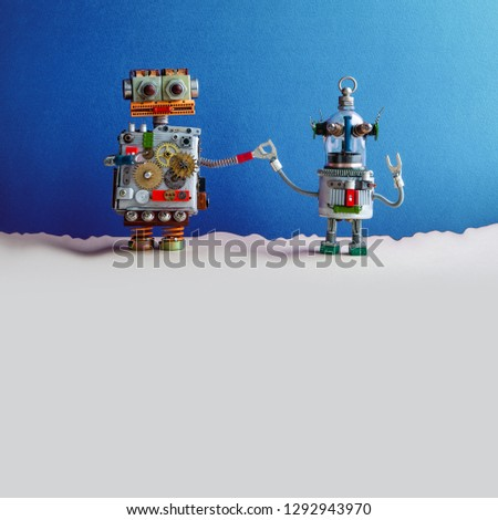 Two funny toy robots holding hands. Fantastic blue beige landscape. The big robot holds the hand of a small glass head robotic ufo humanoid. Copy space.