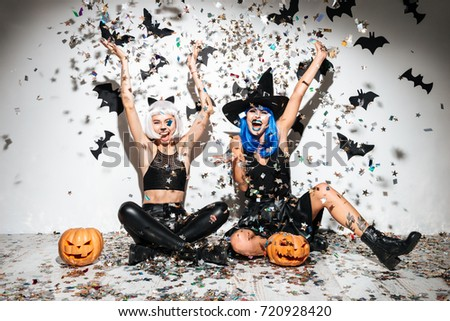 Two funny young women in leather halloween costumes posing with curved pumpkins over bats and confetti background