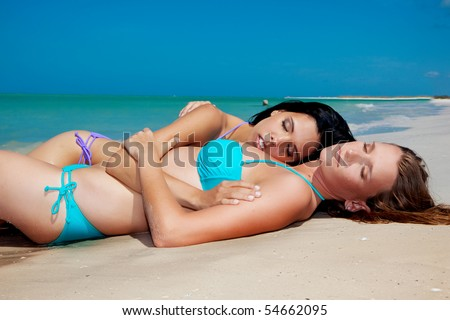 Two gay girls at the beach enjoying the sun