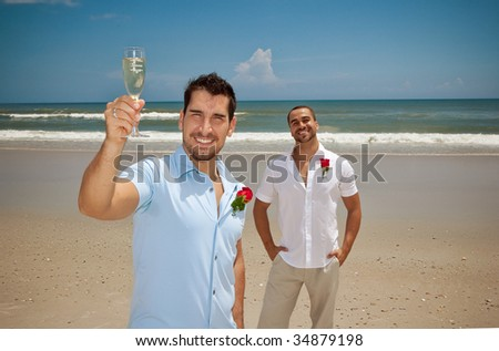 """Two gay man after wedding ceremony, one holding glass with the word """"groom"""""""