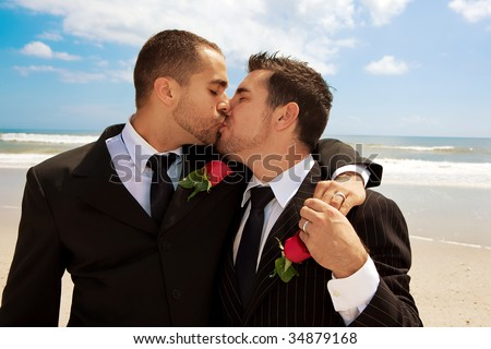 Two gay men after wedding on a beach, kissing - stock photo