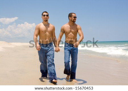 Two gay men in jeans walking on a beach