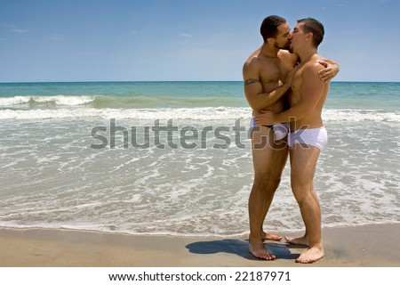 Two gay men standing at the beach, kissing