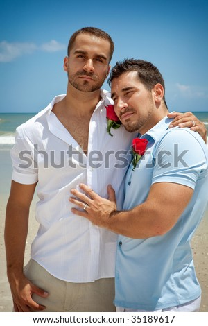 Two gay men standing on a beach after wedding ceremony