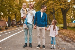 Two gay parents with their adopted daughters walking in park together. Happy LGBT family concept.