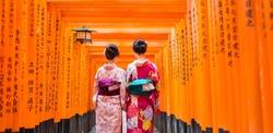Two geishas among red wooden Tori Gate at Fushimi Inari Shrine in Kyoto, Japan. Selective focus on women wearing traditional japanese kimono.
