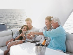Two generational family celebrating with champagne on yacht