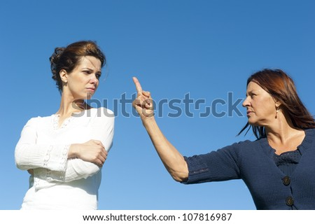 Two  generations, mother and daughter argueing, fighting, communicating. With one arm and finger pointing towards young girl. Isolated with blue sky as background and copy space.