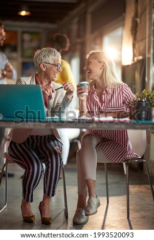 Two generations of female office staff having a good time while chatting in a relaxed atmosphere in the office. Employees, office, work