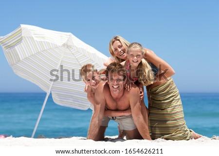 Two generations posing on sandy beach beside sunshade umbrella