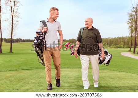 Two generations. Senior and young golf players walking through course with golf equipment.